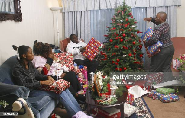 The Frasier family unwrap Christmas gifts at their home on Christmas Day December 25 2004 in Shreveport Louisiana Her husband Marine Corps Reservist...