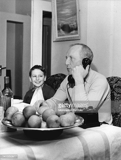 The French actor and singer Bourvil talking on the phone next to his son Dominique 1959