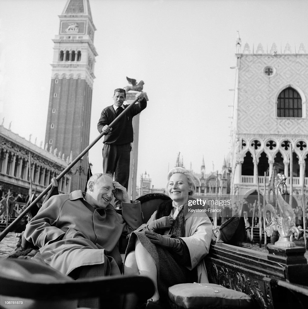 The French Actors Bourvil And Michele Morgan Talking On A Gondola Between Two Takes, During The Shooting Of The Film Le Miroir A Deux Faces (Directed By Andre Cayatte), On Saint Marc'S Square In Venice, In 1958.
