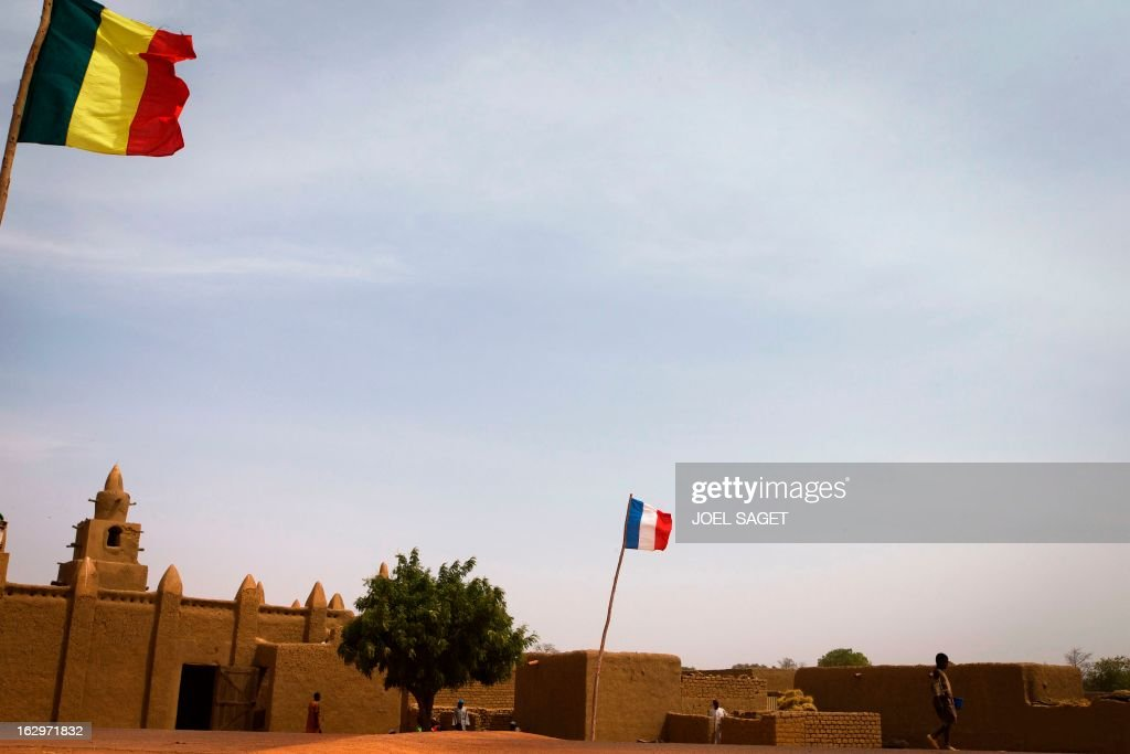 The French and Malian national flags fly outside Bore's mosque, near Mopti, on March 2, 2013. French and Malian troops have been pushing back armed Islamist militant groups for nearly two months, after they gained control of the north of the country during 2012.