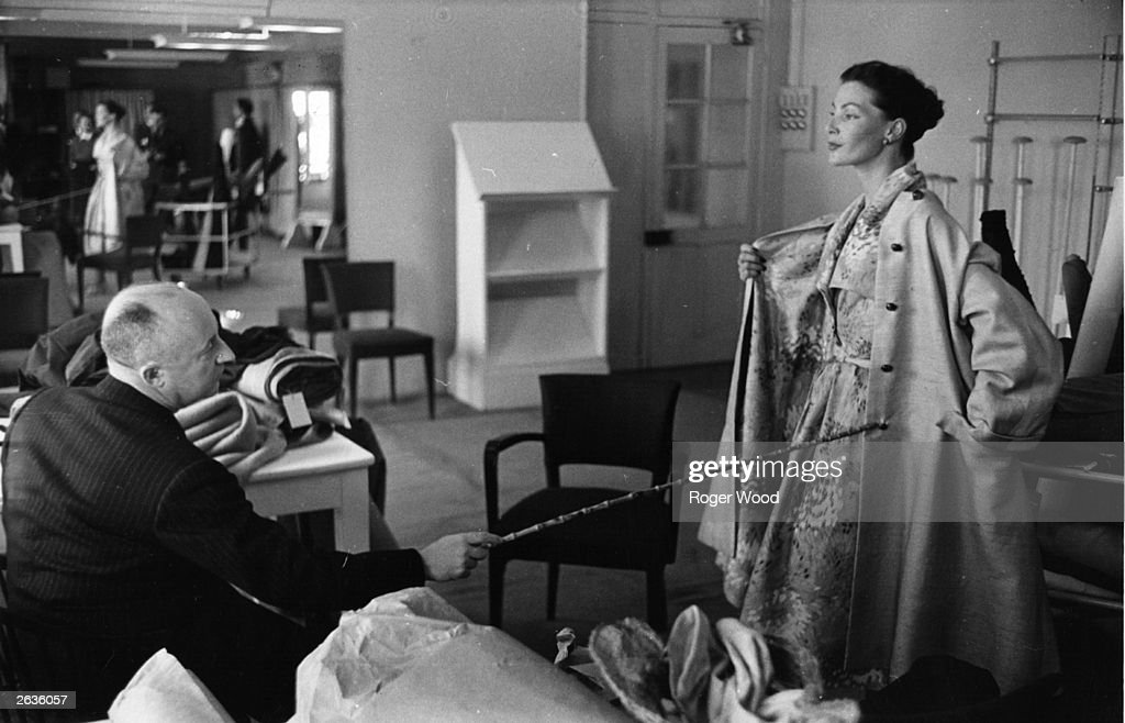 The French couturier Christian Dior (1905 - 1957) inspects one of his designs in his Paris workroom.