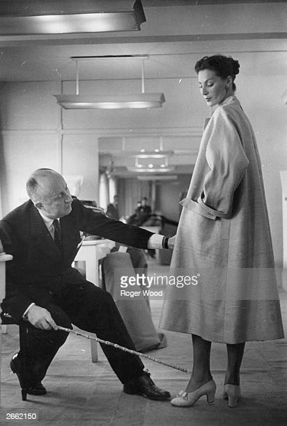 The French couturier Christian Ernest Dior at work in his Paris studio on a coat made from English silks by Seekers
