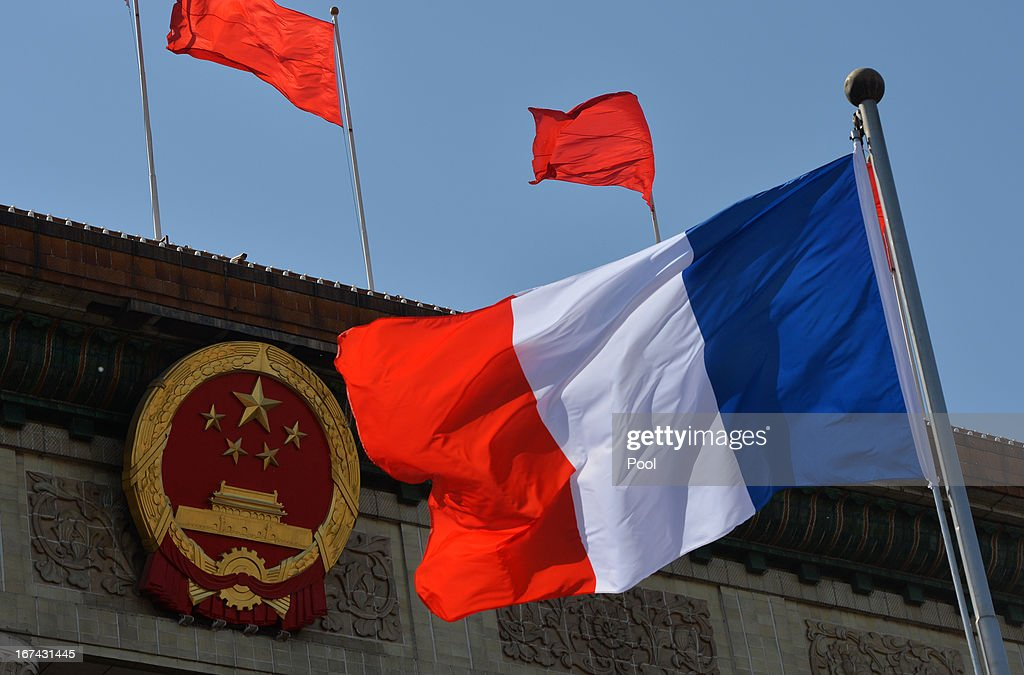 The French flag flies beside the symbol of China as the Chinese President Xi Jinping meets French President Francois Hollande (not pictured) at the Great Hall of the People on April 25, 2013 in Beijing, China. Hollande has begun a two day trade visit to China bringing with him a large French trade delegation.