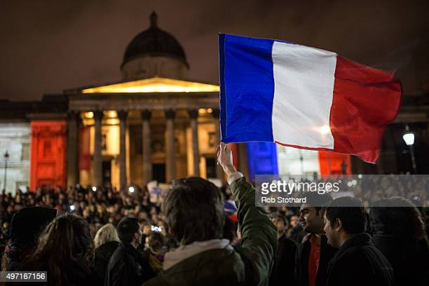 The french flag is held as people hold a vigil for victims of the Paris terrorist attacks in Trafalgar Square on November 14 2015 in London England...