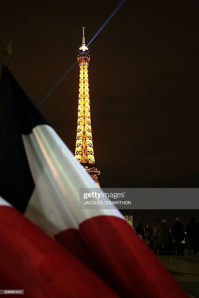 The French flag is photographed against the Eiffel Tower as people attend a gathering initiated by French far-right political group SIEL in support of former general Christian Piquemal, on February 11, 2016 on the Human Rights square in Paris. Piquemal, a former general with the prestigious French foreign legion from 1994 to 1999, was arrested in the French port of Calais on February 6 after scuffles with police at a banned rally in support of a Europe-wide initiative by the Islamophobic Pegida movement. / AFP / JACQUES DEMARTHON
