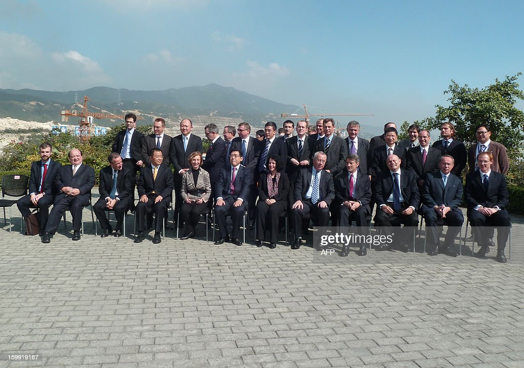 The French Minister for Foreign Trade Nicole Bricq (Front row 6th L) poses for a photograph alongside the President of the Taishan Nuclear Power Joint Venture Company (TNPJVC) Gaoli Gand (Front 7th L), the CEO of France's state-owned electricity company EDF Henri Proglio (Front 4th L), the French ambassador to China Sylvie-Agnes Bermann (Front 6th R), the President of French nuclear company AREVA Luc Oursel (Front 5th R), and French socialist MP Jean-Marie Le Guen (Front 3rd R), as well as other French and Chinese officials of the Taishan Nuclear Power Joint Venture Company (TNPJVC), during a visit and presentation on progress being made in building two new French-designed EPR nuclear power plants, Taishan 1 and 2, in Taishan, on January 22, 2013. The construction of the two Taishan nuclear power plants involves a 6 billion euro investment and 16 000 workers, and is managed by the joint French-Chinese venture Taishan Nuclear Power Joint Venture Company (TNPJVC), which is owned 70% by Chinese energy giant CGNPC and 30% by the French state-owned electricity company EDF. China, whose energy production is dominated by a 70 % use of coal, is the country in the world currently building the most nuclear plants.