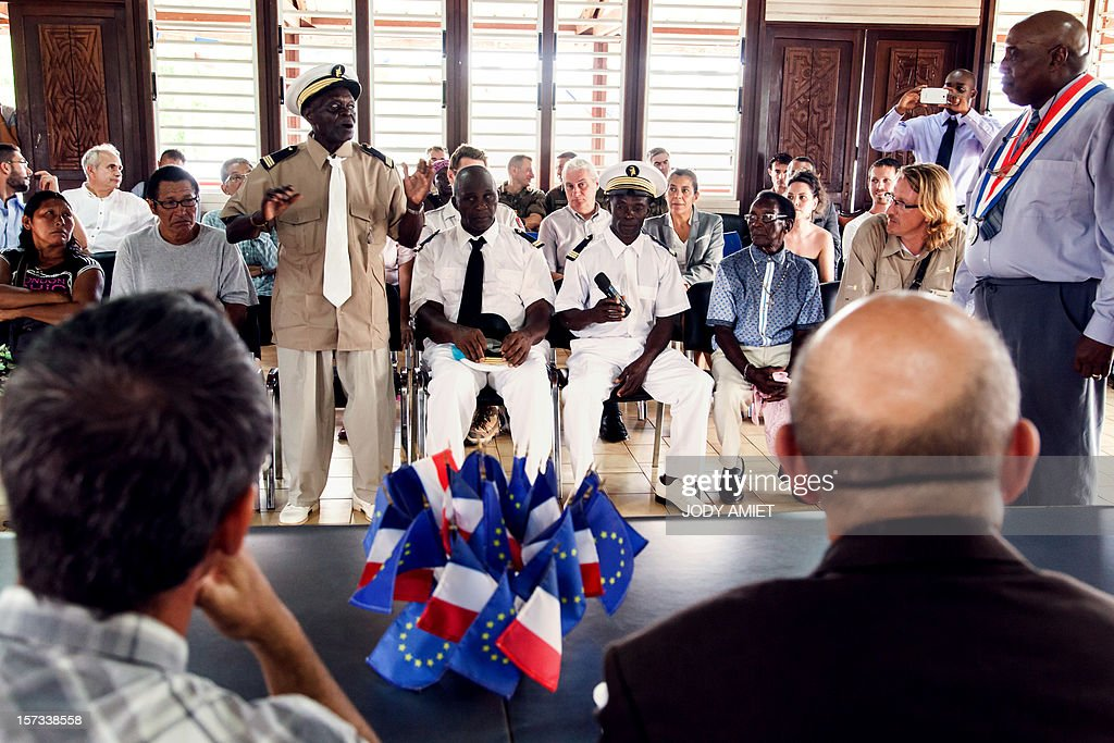 The French Minister of Defence Jean-Yves Le Drian (Bottom R) listens to a local leader during a meeting with leaders of various ethnic tribes which live on the sides of the Maroni river, at the town hall in Maripasoula, on December 1, 2012. Le Drian was in French Guyana to pay his respects to two soldiers killed in the area by illegal gold miners on June 27, 2012.