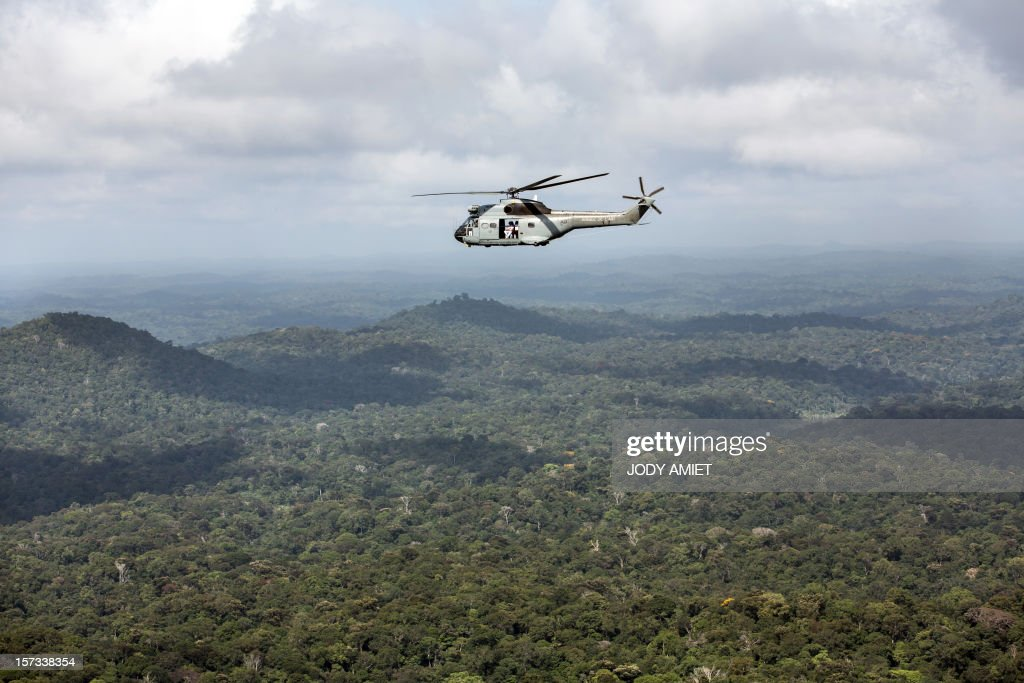 The French Minister of Defence Jean-Yves Le Drian sits in a helicopter on his way to visit the Dorlin military camp and its surroundings, located near gold mining sites, on December 1, 2012. Le Drian was in French Guyana to pay homage to two soldiers killed in the area by illegal gold miners on June 27, 2012.