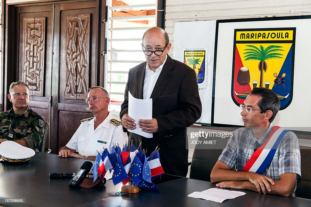 The French Minister of Defence Jean-Yves Le Drian (C) stands alongside the Prefect of Maripasoula, Denis Labbe (2nd L), and its deputy mayor Tristan Bellardie (R), during a meeting with leaders of various ethnic tribes, at the town hall in Maripasoula, on December 1, 2012. Le Drian was in French Guyana to pay his respects to two soldiers killed in the area by illegal gold miners on June 27, 2012.