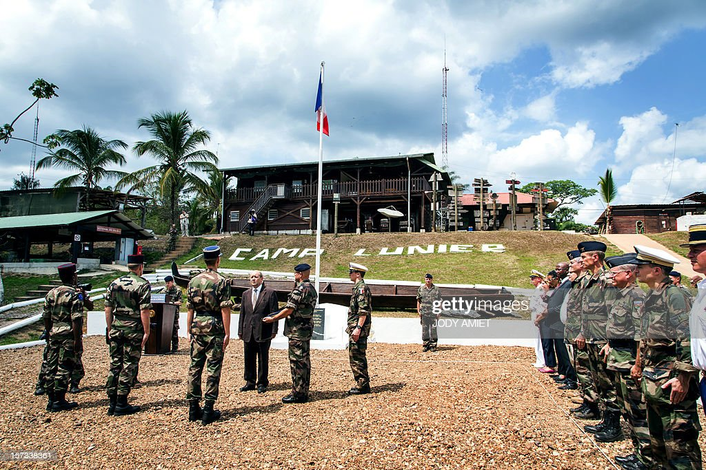 The French Minister of Defence Jean-Yves Le Drian (4th L) takes part in a ceremony in hommage to two soldiers killed by illegal gold miners, at the Dorlin military camp, on December 1, 2012. Le Drian was in French Guyana to pay his respects to two soldiers killed in the area by illegal gold miners on June 27, 2012.