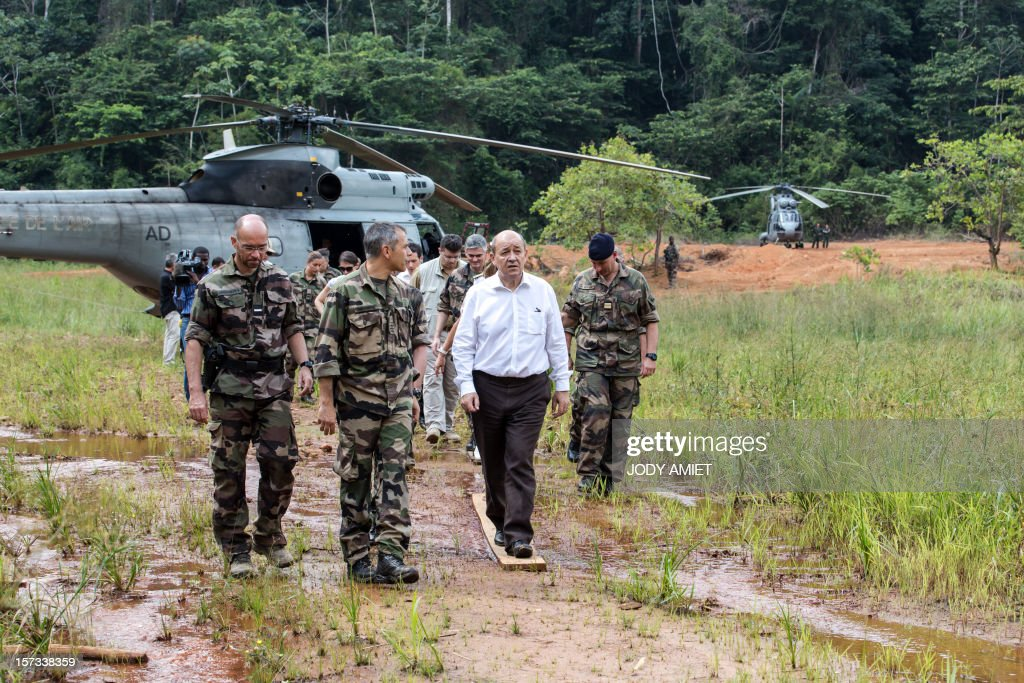 The French Minister of Defence Jean-Yves Le Drian (Front R) walks alongside soldiers and army officers during a visit of the Dorlin military camp and its surroundings, also located near a gold mining site, on December 1, 2012. Le Drian was in French Guyana to pay homage to two soldiers killed in the area by illegal gold miners on June 27, 2012.