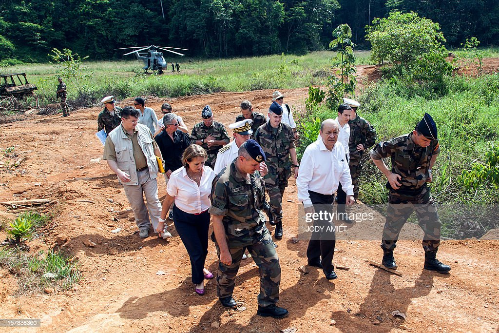 The French Minister of Defence Jean-Yves Le Drian (Front 2nd R) walks alongside soldiers and army officers during a visit of the Dorlin military camp and its surroundings, also located near a gold mining site, on December 1, 2012. Le Drian was in French Guyana to pay homage to two soldiers killed in the area by illegal gold miners on June 27, 2012.