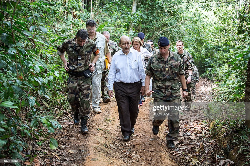 The French Minister of Defence Jean-Yves Le Drian (C) walks alongside soldiers and army officers during a visit of the Dorlin military camp and its surroundings, also located near a gold mining site, on December 1, 2012. Le Drian was in French Guyana to pay homage to two soldiers killed in the area by illegal gold miners on June 27, 2012. AFP PHOTO / JODY AMIET