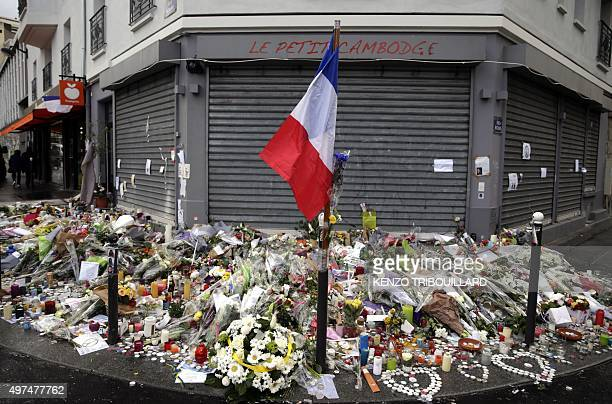 The French national flag candles and flowers are seen on November 17 2015 at a makeshift memorial in front of the 'Le petit Cambodge' restaurant in...