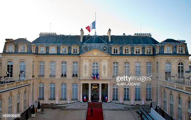 The French national flag flies at half mast on the Elysee presidential palace on December 6 2013 in Paris as a tribute to late Nelson Mandela who...