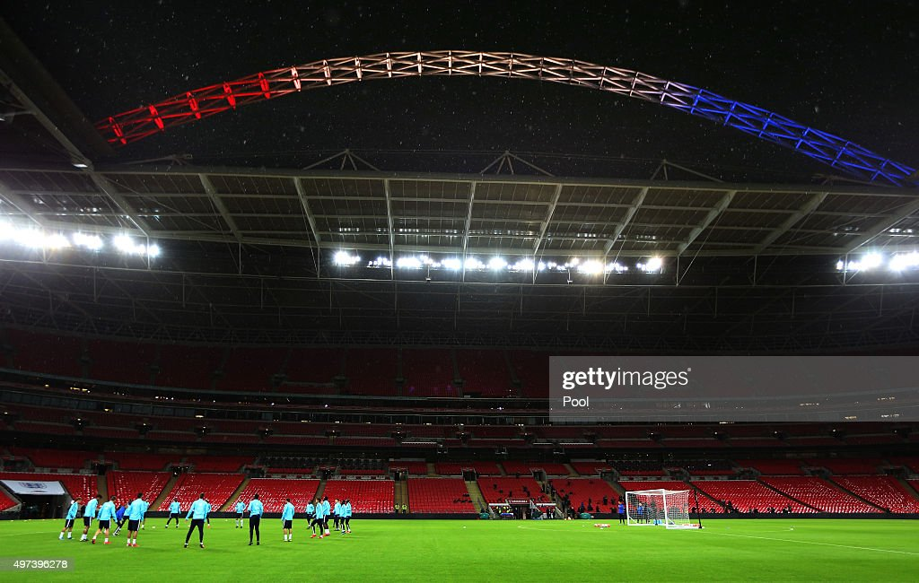 The French players run through their drills under the Wembley arch, lit up in the colours of the French Tricolore during the France training session at Wembley Stadium on November 16, 2015 in London, England.
