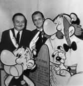 The French Scriptwriter Rene Goscinny And Illustrator Albert Uderzo Holding A Huge Drawing Of The ComicStrip Heroe Asterix One Of Its Adventure Was...