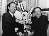 The French Scriptwriter Rene Goscinny And Illustrator Albert Uderzo Holding A Huge Drawing Of The ComicStrip Heroe Asterix One Of Its Adventure Wwas...