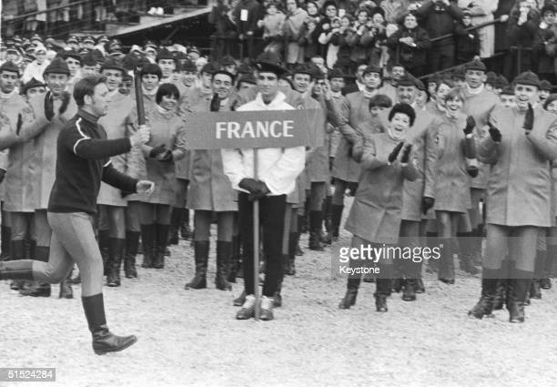 The French team watch French figure skating champion Alain Calmat carrying the Olympic Flame to the start of the 1968 Grenoble Winter Olympics 6th...