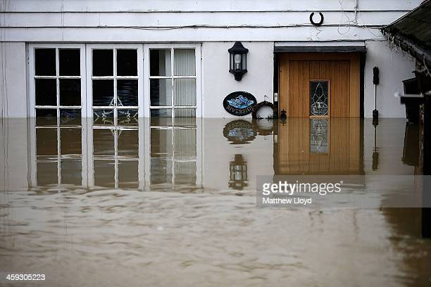 The front door of a house stands submerged by floodwater on December 25 2013 in Yalding England Christmas plans have been badly affected for...