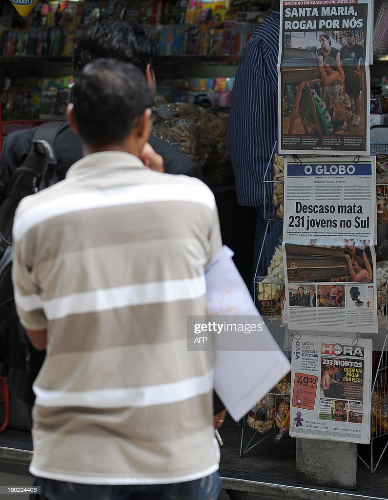 The front pages of the main Brazilian newspapers in a newsstand in Rio de Janeiro, Brazil, on January 28, 2013 have images and headlines related to the tragedy that occured on the eve in the southern city of Santa Maria, when a blaze in a disco killed 233 youngsters. A massive blaze at a nightclub in Brazil killed more than 230 people and left relatives desperately searching for loved ones as horrific accounts emerged of a tragic rush to escape the inferno. AFP PHOTO/VANDERLEI ALMEIDA