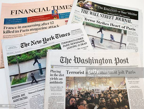 The front pages of various newspapers available in the US related to the attack on French satirical weekly Charlie Hebdo in Paris are viewed on...