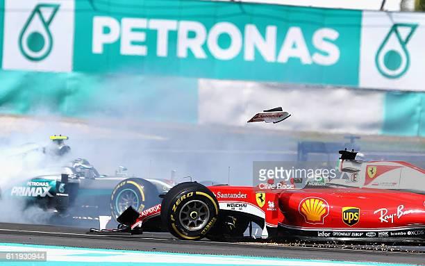 The front wing of Sebastian Vettel of Germany driving the Scuderia Ferrari SF16H Ferrari 059/5 turbo flies into the air as Nico Rosberg of Germany...