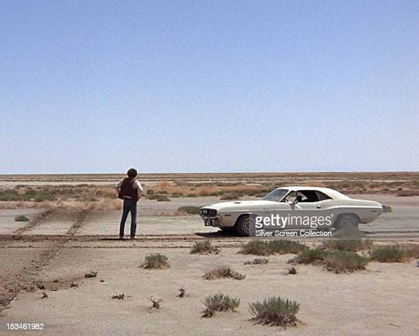 The fugitive Kowalski played by American actor Barry Newman stands in the desert next to his Dodge Challenger in a scene from 'Vanishing Point'...