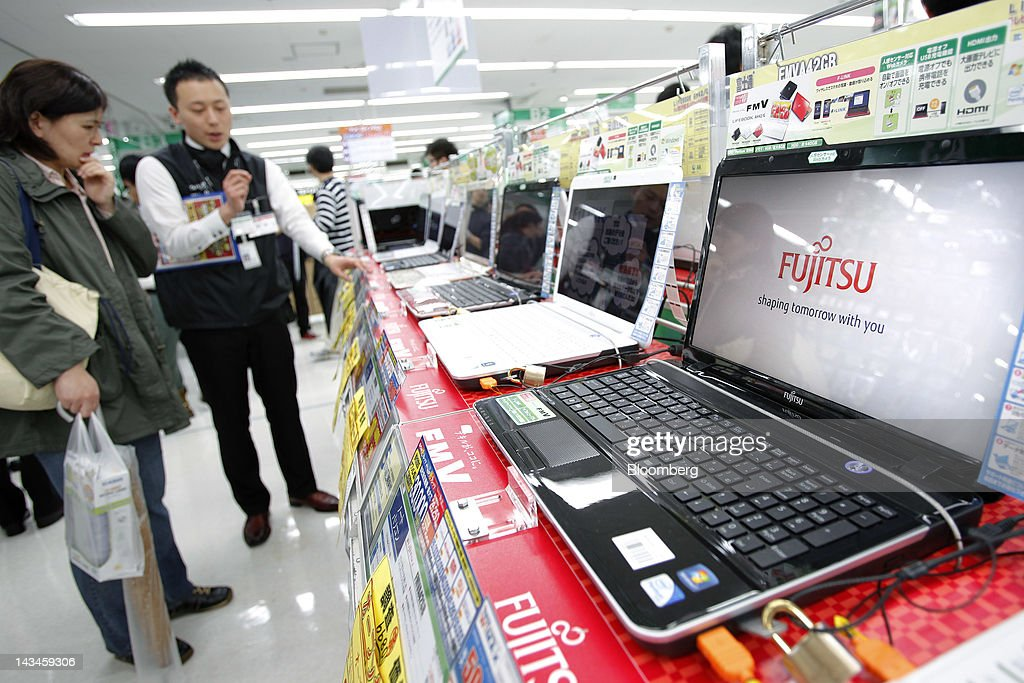 The Fujitsu Ltd. logo is displayed on the company's FMV laptop computer as a sales clerk speaks to a customer at the Labi Ofuna electronics store, operated by Yamada Denki Co., in Yokohama City, Kanagawa Prefecture, Japan, on Friday, April 27, 2012. Fujitsu Ltd. forecast the first increase in profit in three years on increasing sales of services and equipment related to cloud computing and on cost cuts including the sale of its chip factory in Iwate, Japan. Photographer: Kiyoshi Ota/Bloomberg via Getty Images