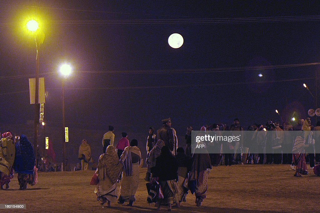 The full moon is pictured as devotees gather at Sangam, the confluence of the rivers Ganges and Yamuna and mythical Saraswati, on Paush Purnima during the Maha Kumbh Mela in Allahabad early on January 27, 2013. The Kumbh Mela in the Indian town of Allahabad will see up to 100 million worshippers gather over the next 55 days to take a ritual bath in the holy waters, believed to cleanse sins and bestow blessings