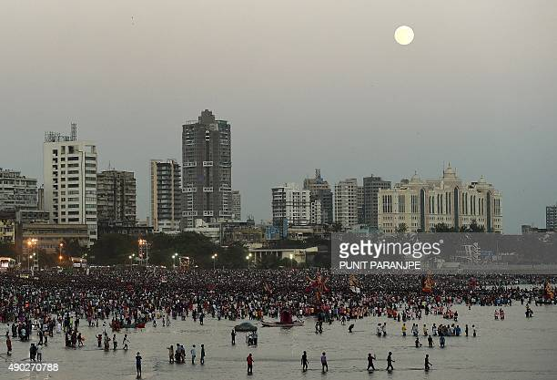 The full moon is seen on the city skyline as Indian devotees carry statues of elephantheaded Hindu god Lord Ganesha for immersion in the Arabian sea...