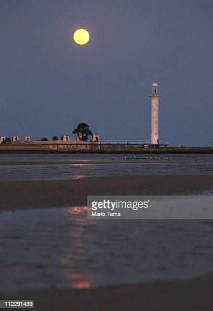 The full moon rises over Biloxi's beach and lighthouse April 17 2011 in Biloxi Mississippi Biloxi's beaches continue to be impacted by tar balls and...