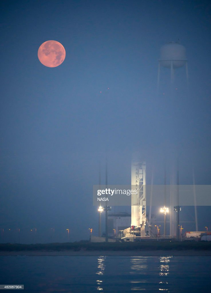 The full Moon sets in the fog behind the Orbital Sciences Corporation Antares rocket, with the Cygnus spacecraft onboard, on July 12, 2014, at NASA's Wallops Flight Facility, Wallops Island, Virginia. The Antares will launch with the Cygnus spacecraft filled with over 3,000 pounds of supplies for the International Space Station, including science experiments, experiment hardware, spare parts, and crew provisions.