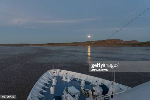 The full moon sets over Western Australia seen over the bow of a ship.