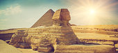 The full profile of the Great Sphinx with the pyramid  in the background in Giza. Egypt. Filtered image:cross processed vintage effect.