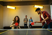 Shot of an attractive young couple playing table tennis while their friends are watching