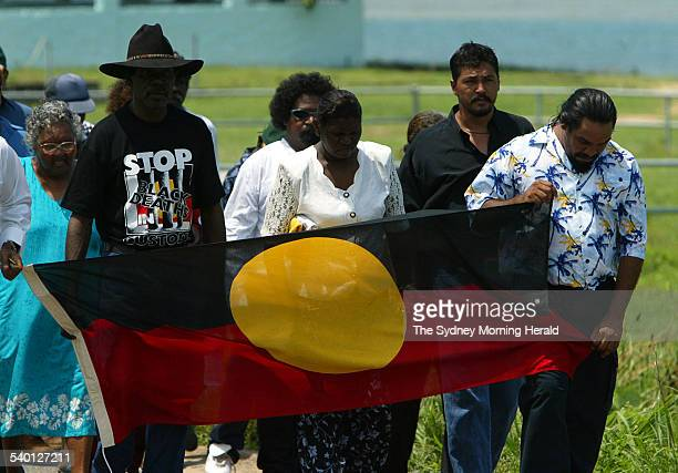 The funeral procession including activist Murrandoo Yanner second from right walks to the church during the funeral of Cameron Doomadgee who died in...