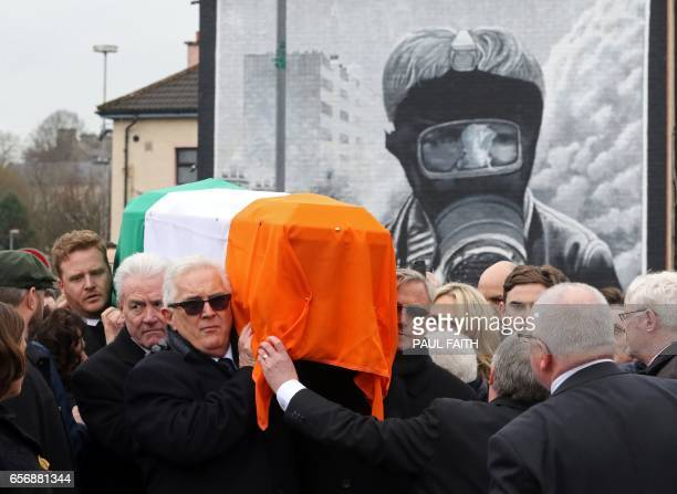 TOPSHOT The funeral procession passes a Republican mural as it makes it's way with the coffin to St Columba's Church Long Tower for the funeral of...