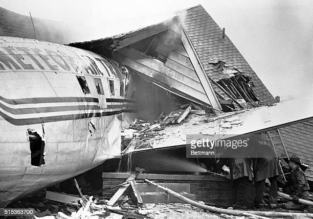The fuselage of a DC3 cargo plane lies under the wreckage of the house into which it crashed while coming in for a landing at City Airport in Detroit...