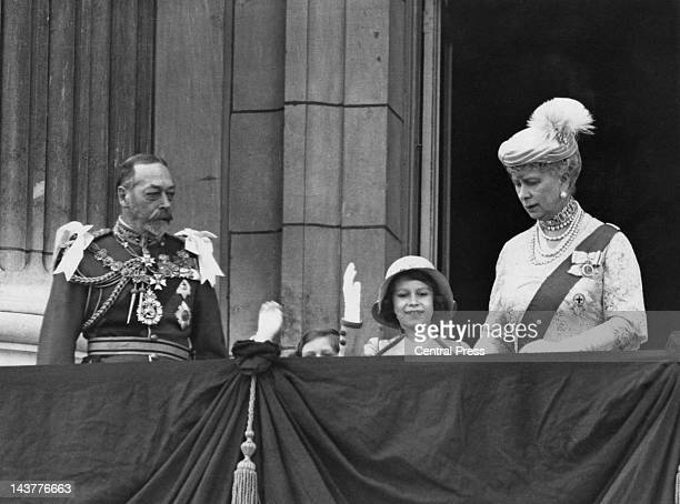 The future Queen Elizabeth II waving from the balcony of Buckingham Palace in London with her younger sister Margaret and her grandparents King...