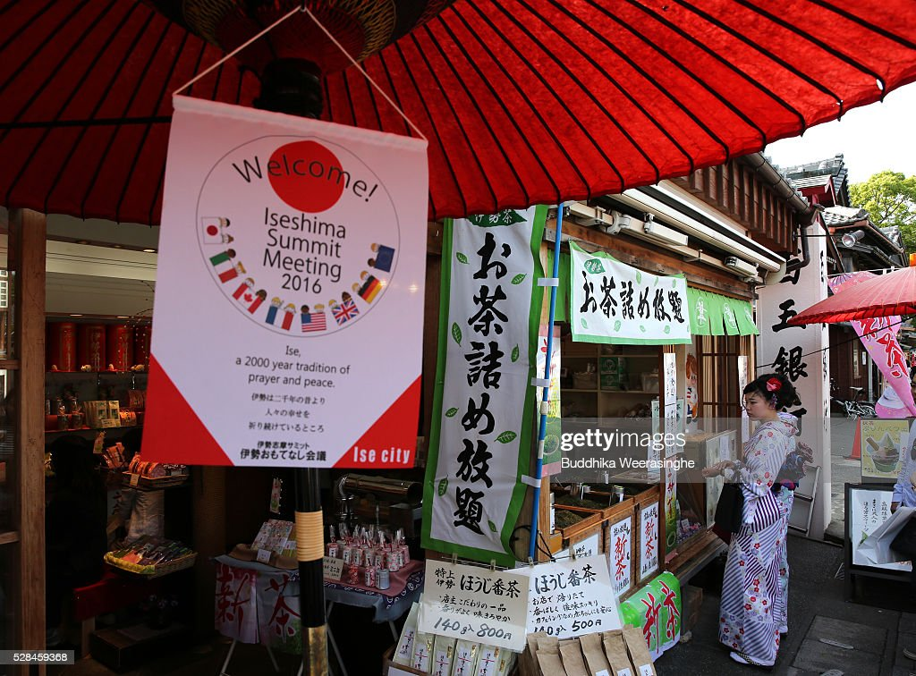 The G7 Ise-Shima summit welcome flag hangs below the traditional Japanese tea ceremony umbrella in front of the SUI Tea Shop as a woman dressed in traditional kimono is served at Okage Yokocho, a traditional shopping street on May 5, 2016 in Ise, Japan. Ise-Shima prepares for the G7 summit which is to be held on May 26 and 27, 2016.