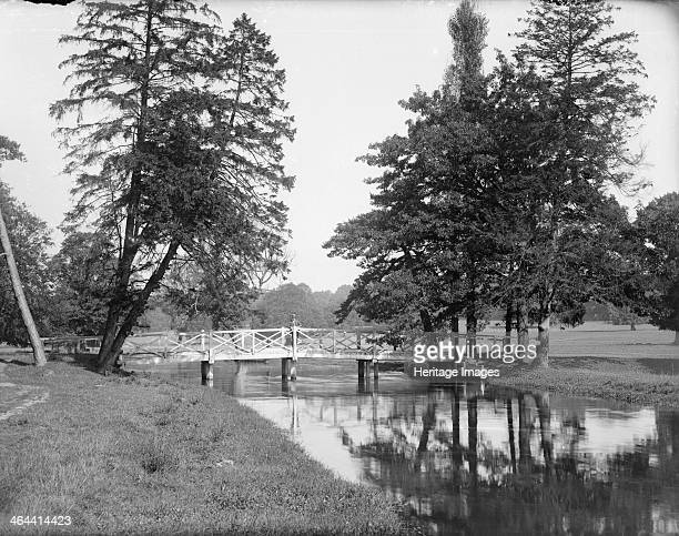 The Gade Bridge in Cassiobury Park Watford London c1860c1922 A man possibly one of the photographer Henry Taunt's assistants is standing in the centre