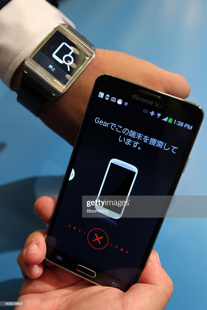 The Galaxy Gear watch, left, and Galaxy Note 3, manufactured by Samsung Electronics Co., are displayed at a news conference announcing NTT DoCoMo Inc's new smartphone models in Tokyo, Japan, on Thursday, Oct. 10, 2013. DoCoMo President Kaoru Kato said he is watching the price of mobile phones after SoftBank Corp. acquired Sprint Corp. Photographer: Junko Kimura/Bloomberg via Getty Images