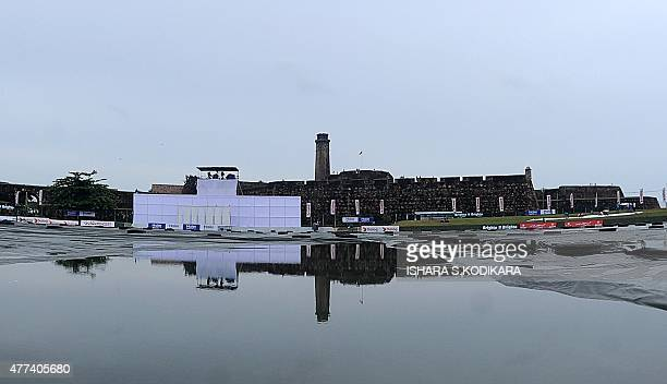 The Galle Fort is reflected in water lying on plastic sheeting over the playing surface after rain showers delayed play during the first day of the...