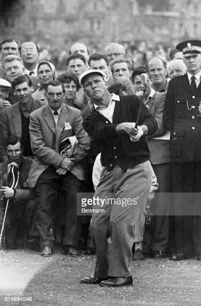 The gallery intently watches a shot made by American golfer Arnold Palmer as he competes in a qualifying round of the 1960 British Open in St Andrews...