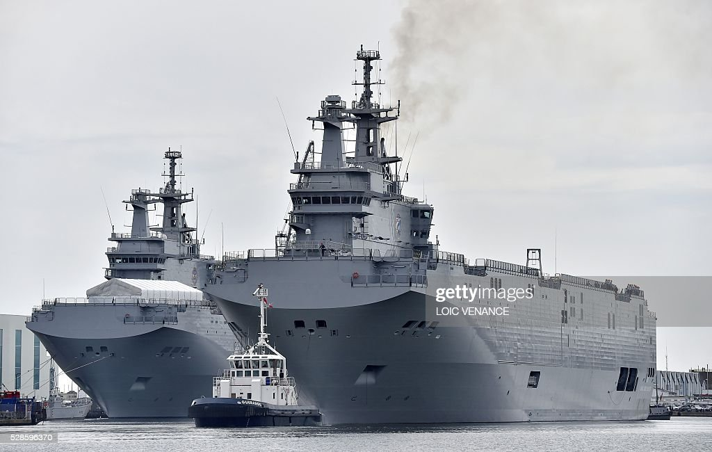 The Gamal Abdl Nasser (ex-Vladivostok) Mistral class ship (R) leaves the harbor for a one week training session next to its twin ship, ex-Sebastopol, on May 6, 2016 in Saint-Nazaire, western France. The 'Nasser', first one of the two Mistral class ships sold by France to Egypt after its first sale cancellation to Russia, leaves Saint-Nazaire (Loire-Atlantique) on Friday for a week of Egyptian crew training at sea. / AFP / LOIC