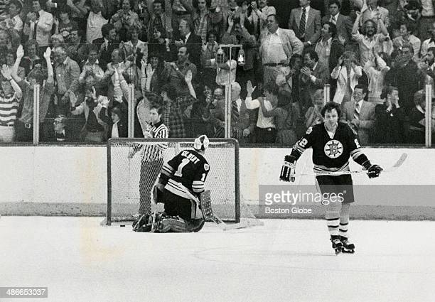 The gamewinning goal made by Montreal Canadiens player Yvon Lambert not pictured sits in the net behind Boston Bruins goalie Gilles Gilbert as...