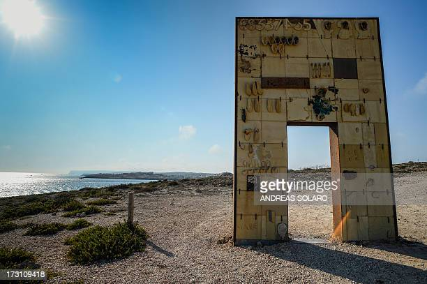 The Gate of Europe a monument which pays tribute to migrants arriving on the Italian island of Lampedusa is seen near the Lampedusa harbour on July 7...