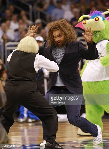 The 'Geico' caveman actor dances with an arena worker while the Miami Heat play against the Orlando Magic at Amway Arena on February 3 2011 in...