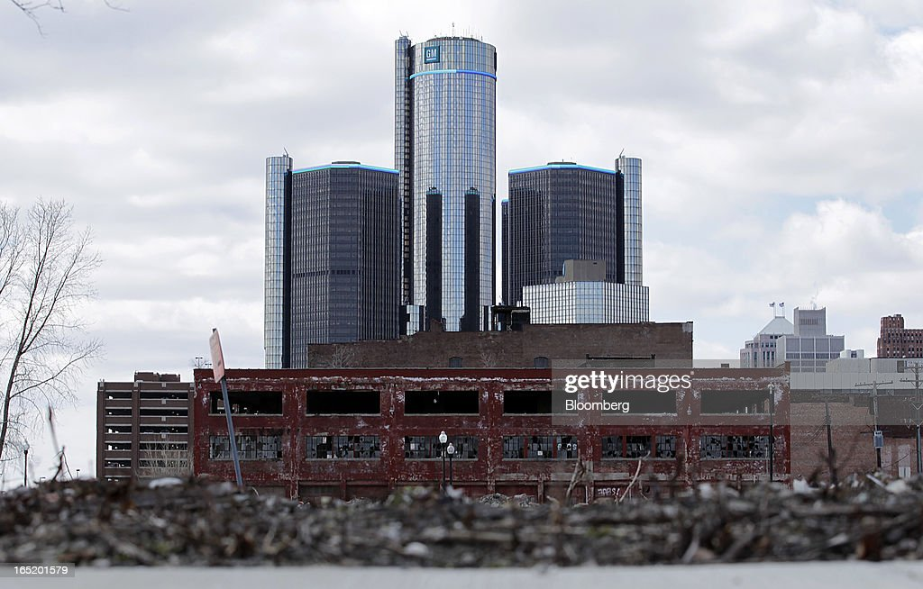 The General Motors Co. (GM) headquarters building is seen in the distance past a run down building in Detroit, Michigan, U.S., on Monday, April 1, 2013. U.S. automakers are surging, while Detroit is in such distress that it's being taken over by the state of Michigan today. Photographer: Jeff Kowalsky/Bloomberg via Getty Images